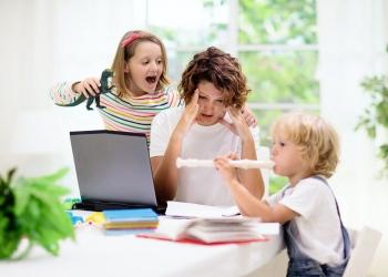 Madre trabajando desde casa con niños.