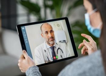 Mujer enferma con máscara protectora durante la videollamada con su médico.