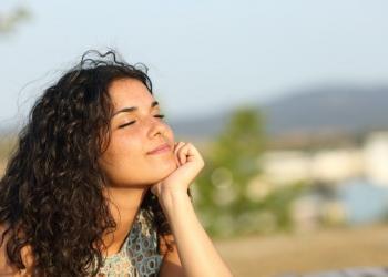 Mujer relajada disfrutando del sol en un cálido parque al atardecer.