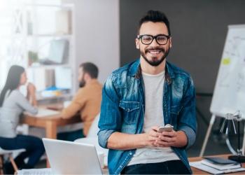 Hombre Joven sostiene teléfono inteligente y mirando a la cámara en el trabajo.