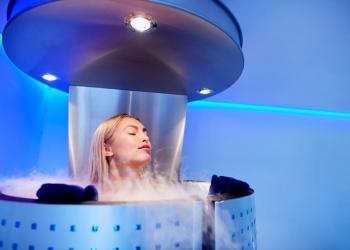Mujer en una criosauna recibiendo terapia criogénica en una clínica de cosmetología.