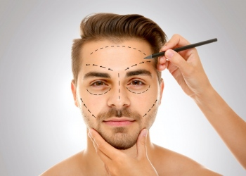 Cirujano dibujando marcas en la cara de un hombre