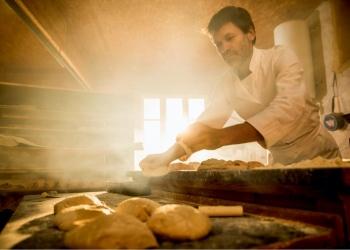 En una panadería artesanal, un panadero prepara la masa de pan.