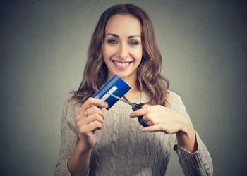 Mujer alegre que corta tarjetas de crédito después de pagar su deuda.