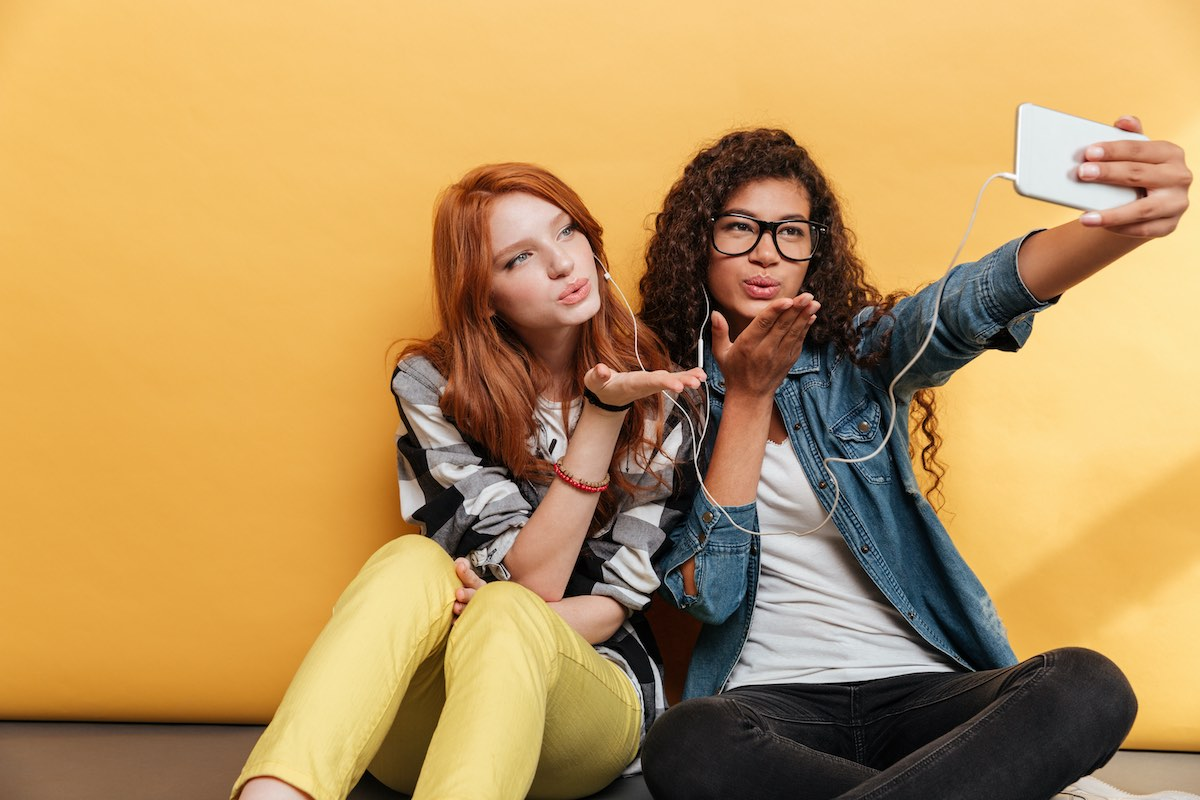 Dos chicas tomando una selfie con teléfono móvil