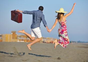 Pareja en la playa con maletas de viaje