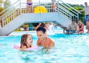 Madre en bikini jugando con su hija en la piscina de un parque acuático.