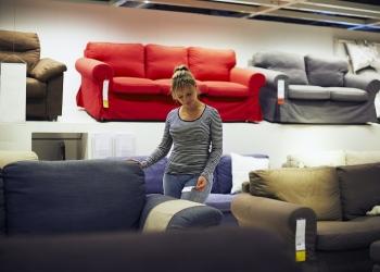 Mujer comprando muebles, sofá y decoración para el hogar en una tienda.