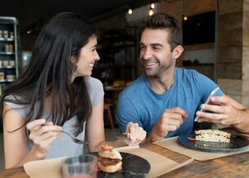 Pareja comiendo juntos en un café y mirando las redes sociales en un teléfono celular