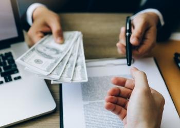 Contrato de venta y entrega de dinero en efectivo y bolígrafo al empresario.