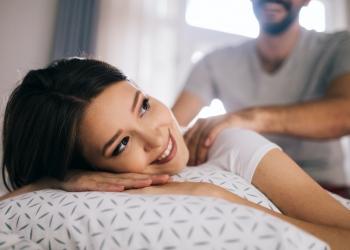 Novio dando masaje a su novia descansando en una cama.