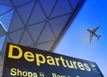 Señal de salida en un aeropuerto y un avión volando.
