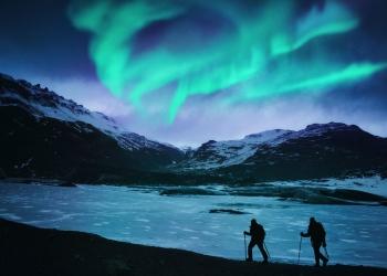 Excursionistas bajo la aurora boreal en Islandia.