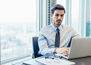 Joven empresario trabajando en su oficina, en su computadora