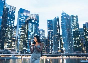 Mujer asiática mirando un teléfono inteligente con la ciudad detrás.