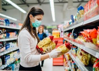Mujer con mascarilla comprando comida en el supermercado.