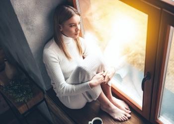 Mujer joven mirando por la ventana mientras bebe una taza de café.