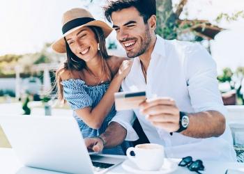 Pareja joven con tarjeta de crédito y computadora portátil