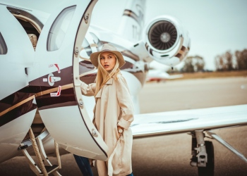 Joven mujer rubia rica entrando en un avión privado estacionado en el aeropuerto.