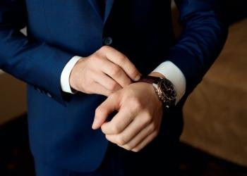 Hombre de negocios en traje y ajusta su reloj, preparándose para una reunión.