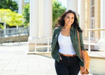 chica latina con bolsa viajando caminando por la calle de la ciudad.