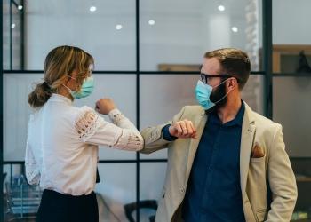 Colegas en la oficina practicando saludos alternativos por seguridad y protección durante COVID-19