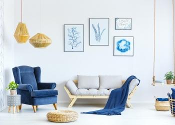 Sala de estar con sofá, sillón, lámpara, pósters.