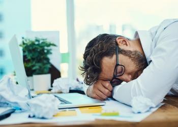 Empresario cansado con la cabeza gacha sobre un escritorio en la oficina.