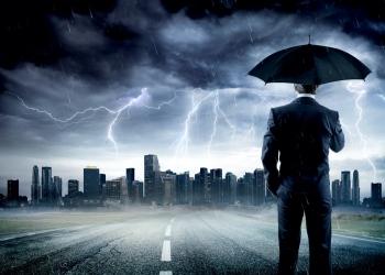 Empresario con paraguas mirando la tormenta sobre la ciudad