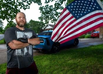 Hombre calvo con barba en el patio delantero de su casa, bandera estadounidense y muscle car