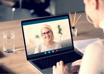 Mujer joven habla en una videollamada en la computadora con una mujer anciana sonriente.