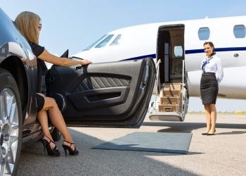 Mujer saliendo del automóvil estacionado frente a un avión privado y azafata.
