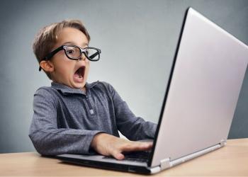 Niño sorprendido encomputadora portátil.