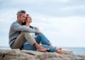 Pareja de mediana edad sentada en una roca en la playa