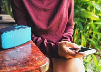 Mujer con teléfono inteligente con altavoz bluetooth
