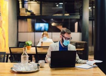 Empresarios con máscaras en la oficina y trabajando a distancia durante la pandemia de COVID-19.