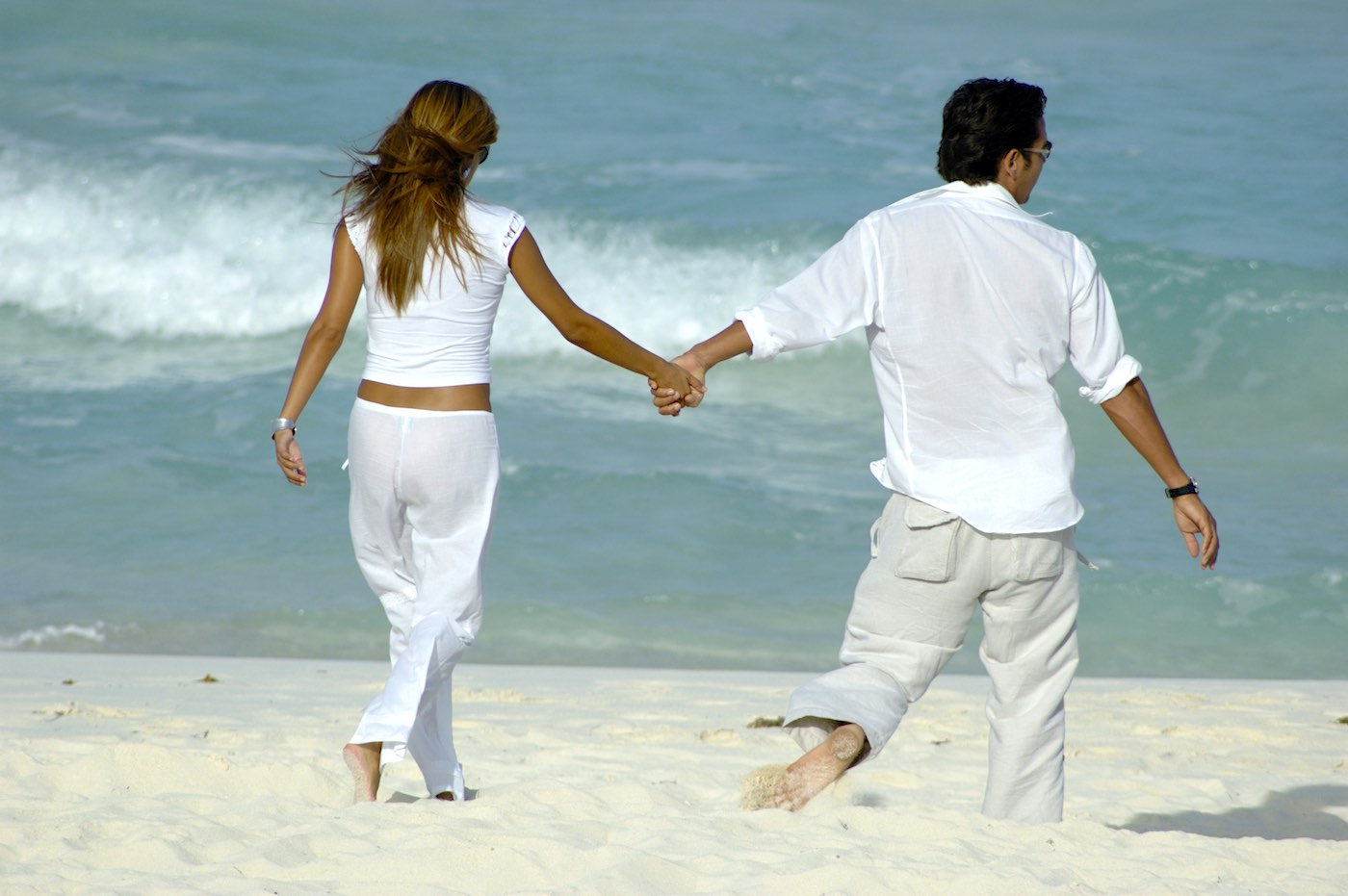 Pareja joven caminando por la playa con ropa de lino.