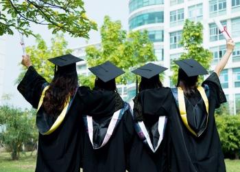 Mujeres graduadas con toga y birrete de graduación en el campus.