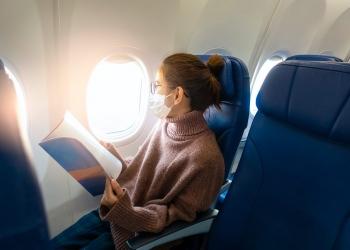 Mujer con máscara facial para COVID-19 está viajando en un avión.