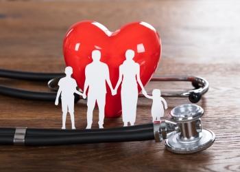 Concepto de seguro médico familiar y estetoscopio en escritorio de madera.