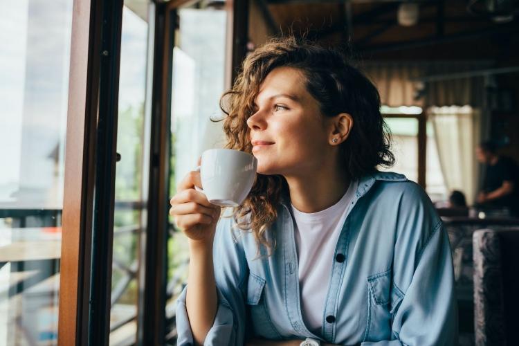 Mujer tomando café mirando por la ventana de un restaurante.