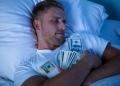 Hombre durmiendo en la cama con paquete de dólares