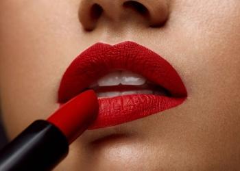 Pintalabios rojo. Hermosa chica aplicando el lápiz labial