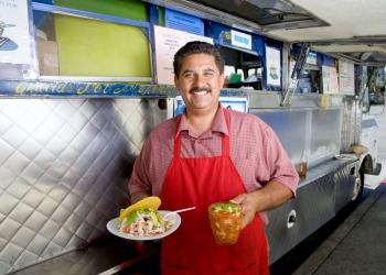 Hombre hispano con merienda y refresco junto a un camión de comida.