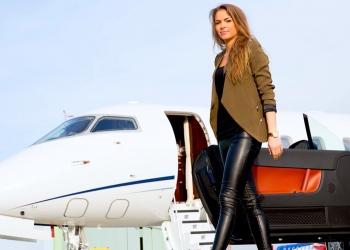 Mujer saliendo de un coche convertible yendo a un jet privado