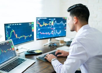 Hombre comerciante de la bolsa de valores usando la computadora en casa.