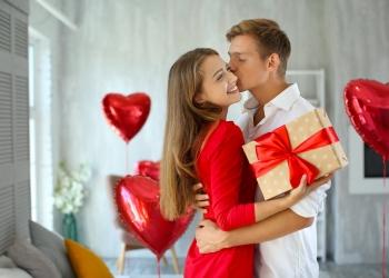 Pareja joven con caja de regalo abrazándose en casa