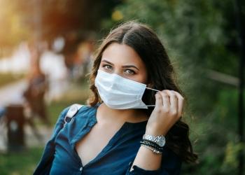 Hermosa mujer con una mascarilla que protege contra la propagación de la enfermedad por coronavirus o SARS-CoV-2.