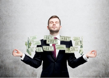 Hombre de negocios meditando y dólares en efectivo entre sus manos.