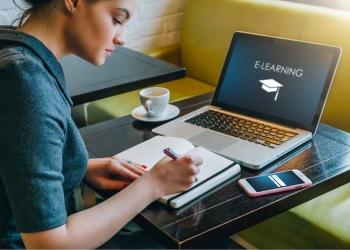 Joven sentada en una mesa de un café frente a ordenador portátil en clases e-learning